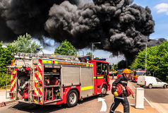British fireman with hose at a large fire Stock Photo