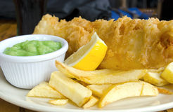 British Fish and Chips. Traditional British Fish and Chips with mushy peas Royalty Free Stock Photography