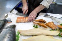 British fish monger slicing, filleting or cutting fresh slamon o