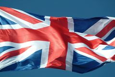British flag. Waving to the wind against the sky royalty free stock photos
