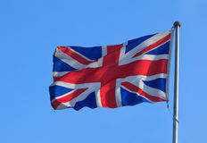 British flag. Waving british flag with blue sky as background Stock Images