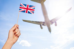 British flag against airplane flying through sky Stock Photo