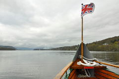 British flag on boat nose on lake. Traveling by boat or ship on a lake, cloudy weather conditions, hilly landscape, smooth lake surface. Suitable as desktop Stock Photography