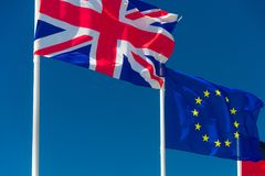 British flag and European flag. Waving against blue sky in Wimereux, France royalty free stock photo