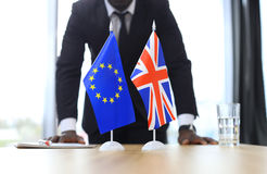 British flag and flag of European Union with businessman near by. Brexit. Stock Photo