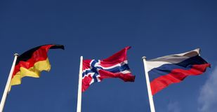 Norway flag, German and Russian. Against the blue sky stock photography