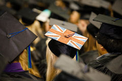 British Flag on Graduate's Cap. A Female student at a graduation ceremony with the British flag painted on her cap listening to the commencement speaker at the Royalty Free Stock Image
