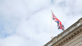 British flag at palace. Horse Guards London. Union jack flag on top of palace and clouds passing by. View from ground looking up stock footage
