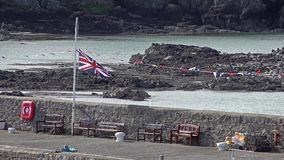 British flag waving halfmast at Cemaes, Wales - United Kingdom. The town with the nuclear power plant stock video