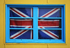 British flag in a window. The British flag in a window. With blue and yellow wall Stock Image