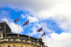 British flags waving in the wind. At the roof of building on Trafalgar square Royalty Free Stock Images