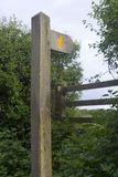 British footpath sign, stile and waymarker. Yellow walker on wooden footpath signpost. Style and waymarker arrow in the background Royalty Free Stock Photo