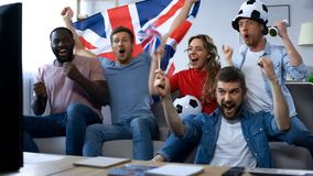 British friends watching football game on tv, rejoicing goal of national team stock photography