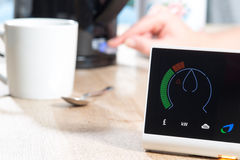 British Gas Smart Meter Measures Home Energy Consumption. A smart meter is displayed on a wooden surface near mug and spoon and a kettle which is being switched stock photo