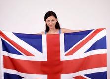 British girl smiling holding up the UK flag. Stock Photo