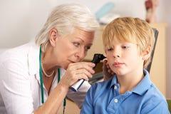 British GP examining young boy's ear Stock Photography