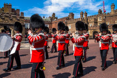 British guardsmen march down opposite St. James Palace. The Mall. London. UK. British guardsmen march down opposite St. James Palace. Selective focus.  London Stock Photos