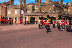 British guardsmen march down opposite St. James Palace. The Mall. London. UK. British guardsmen march down opposite St. James Palace. Selective focus.  London Royalty Free Stock Photography