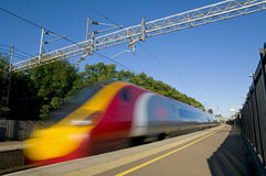 British High Speed Train. A British high speed passenger train passing through a station in the early morning Royalty Free Stock Images