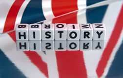 British history. Text ' history ' in uppercase black letters on small white cubes on reflective surface with Union Jack flag superposed stock photography