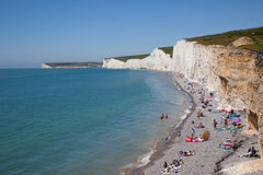 British holiday makers on the beach below white cliffs Stock Image