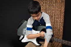 8 year old British Indian boy practices the electric guitar at home. stock images