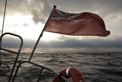 British maritime ensign flag boat and stormy sky Royalty Free Stock Image