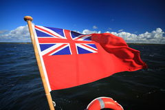 British maritime red ensign flag blue sky. The UK red ensign the british maritime flag flown from a yacht sail boat blue sky and sea Royalty Free Stock Photo