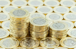 British money, new pound coins in three stacks. British money, new pound coins in three stacks on a background of more money. New one pound coins introduced in Royalty Free Stock Photography