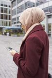 British Muslim Woman Texting On Mobile Phone Outside Office Stock Photos