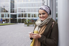 British Muslim Woman Texting On Mobile Phone Outside Office Stock Photography