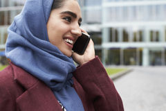 British Muslim Woman Using Mobile Phone Outside Office Royalty Free Stock Image