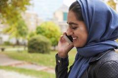 British Muslim Woman Using Mobile Phone In Park Stock Image