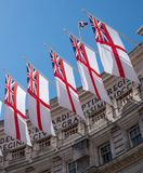 British naval white ensign flags flying at Admiralty Arch between The Mall and Trafalgar Square in the centre of London. UK. British naval white ensign flags royalty free stock image