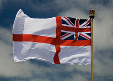 British Navel Ensign (Flag). A photo of the British Royal Naval Flag, flying against a blue sky with some light clouds, and a crown on the top of the flag pole Royalty Free Stock Images