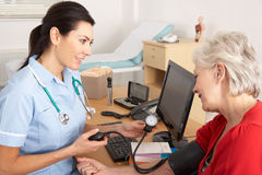 British nurse taking woman's blood pressure Royalty Free Stock Photo