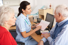 British nurse talking to senior couple. In nurse's office Royalty Free Stock Image