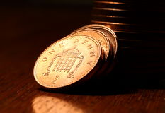 British One Penny. One Penny coins on a wooden surface stock images
