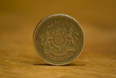 British one pound coin. On a wooden table. Macro with narrow depth of field Stock Images