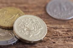 British one pound, Quarter dollar coin, and euro coin on wooden. Table background. The concept of business growth, financial or trade Stock Image