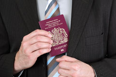 British passport. Businessman presenting a British passport at customs or check in area Royalty Free Stock Photos