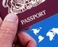British passport. Man holding British passport over world map royalty free stock photo