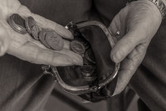 British pensioner putting money in purse. Cost of living. British pensioner putting coins into a purse. Close up of hands. Black and white image. Cost of living Royalty Free Stock Photos