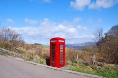 British Phone Booth. Isolated red rural telephone box in the British countryside Royalty Free Stock Image