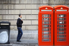 British phone booth. London, England - July 27, 2015: A man passes by some  vintage red telephone booth, in London, England Royalty Free Stock Photo