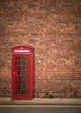 British Phonebox Against Red Brick Wall Royalty Free Stock Images