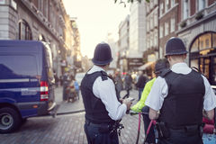 British police constable on London streets. British police officers in helmets policing London streets Stock Images