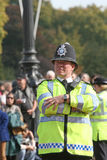 British police officer. Tuesday, October 2, 2007: A british police officer is watching the changing of the guard at Buckingham Palace, in London, UK Stock Image