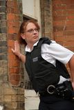 British Police Officer. Female UK Police officer in urban street Royalty Free Stock Photos