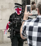 British Police Officer Blended With Union Jack Flag. Outside Crowded Tourist Attraction In London, Double Exposure Blured Candid People taking photo with mobile Stock Photo